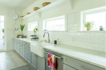a clean white kitchen with large country style sink