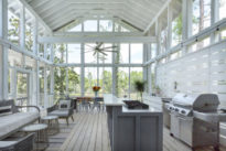a screened in back porch with a outdoor kitchen