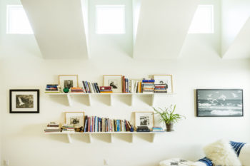 sky lights reflecting on a white wall and white bookshelves